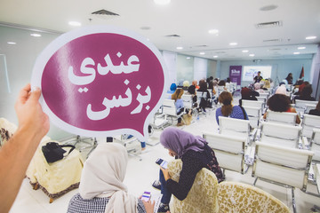 """Hand holding a speech bubble with Arabic sign text """"I have an business"""". Entrepreneur community in Palestine, Ramallah"""