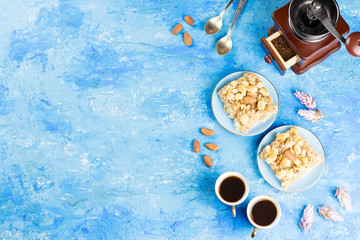 Two coffee cups, coffee grinder and apple pie on blue artistic background.