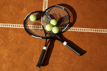 Overview of two tennis rackets with group of balls on top lying on court at stadium