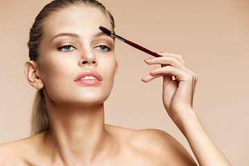 Beautiful woman using brush for brows. Photo of attractive woman with perfect makeup on beige background. Beauty concept