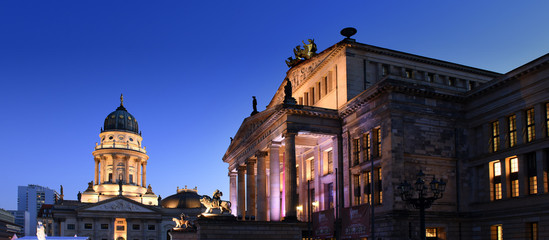 Konzerthaus Berlin with lion statue on Gendarmenmarkt square at night with German cathedral in the...