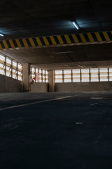 A view of an old parking lot on 3th floor of a parking building in a business district with a low key. Seeing yellow and black traffic sign warning the height of the ceiling.