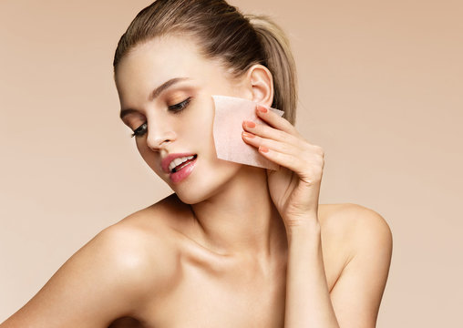 Woman cleaning face with facial cleansing wipes, removing makeup. Photo of woman with perfect skin on beige background. Beauty concept