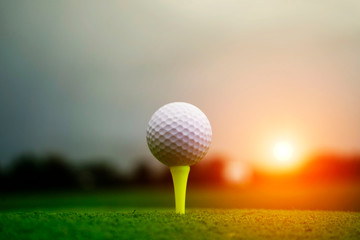 Golf ball on tee in beautiful golf course at sunset background. Golf ball on green in golf course at Thailand