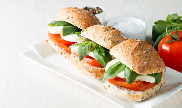 Close-up photo of sandwich, burger with caprese salad with ripe tomatoes, basil, buffalo mozzarella cheese. Italian and Mediterranean food concept.