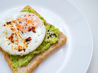 Appetizing bruschetta with egg and avocado on a plate. On the Sandwich, the avocado pulp and fried quail egg. Dark background. View from above. Close-up. Macro photography.