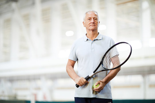 Aged tennis player in activewear standing inside large stadium or modern sports center