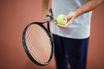 Light green tennis ball in hand of aged tennis player and racket in the other one
