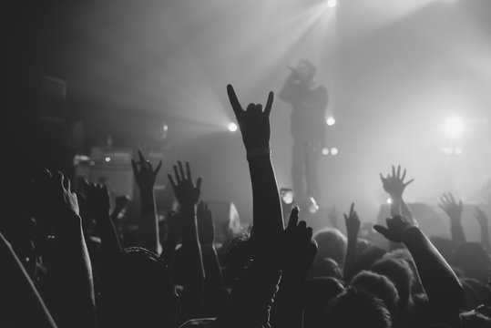 Hands of a crowd raised up at the music show to the singer on stage. Black and white. Black and white