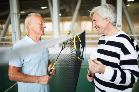 Two friendly senior badminton players in activewear with rackets standing by net and interacting