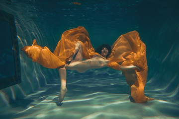 cute sporty girl swims underwater as a free diver in lingerie and mesh catsuit with rhinestones alone Fototapete