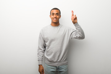 African american man on white wall background with fingers crossing and wishing the best