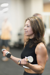 fitness, sport, bodybuilding and weightlifting concept - close up of young woman with dumbbells flexing muscles in gym