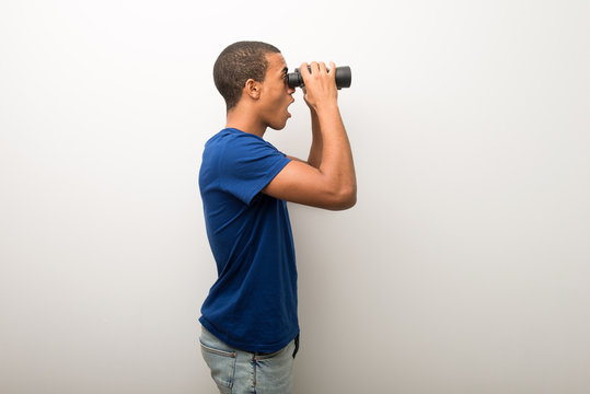 Young african american man on white wall and looking in the distance with binoculars