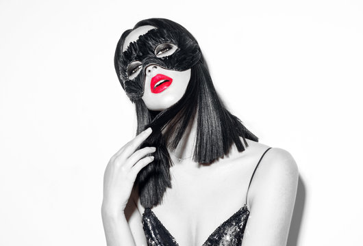 Beauty sexy brunette woman portrait. Girl wearing carnival black feather mask. Black hair, red lips, holiday makeup. Black and white fashion portrait