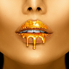 Gold paint drips from the sexy lips, golden liquid drops on beautiful model girl's mouth, creative abstract makeup. Beauty woman face