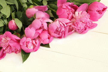 Bouquet of small pink peonies on white painted wooden table. Closeup