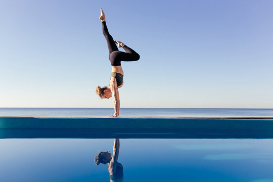 Young attractive woman practicing yoga doing Variation of handstand pose, Pincha Mayurasana. Working out by the pool, above the beach, relaxing against blue sky. Health and beauty concept