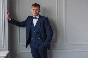 Stylish young man in a business suit a guy in trousers and a vest stylish  grooms morning