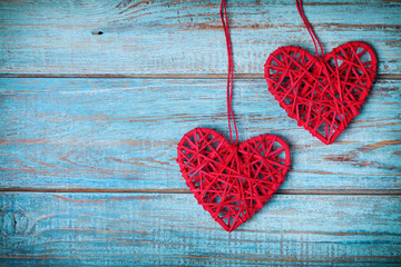Two red heart hanging on turquoise vintage wall for Valentines day card.