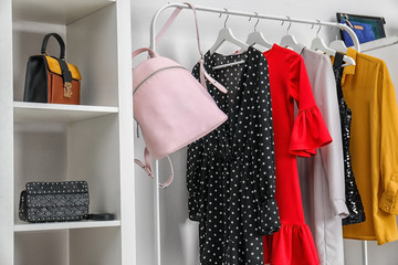 Wardrobe with stylish bags and clothes indoors. Idea for interior design