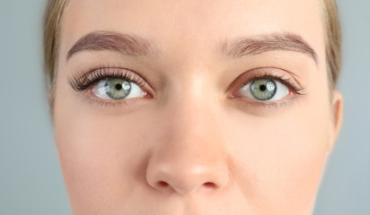 Young woman with beautiful eyelashes on gray background, closeup. Before and after extension procedure