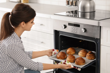 Beautiful young woman taking out tray of baked buns from oven in kitchen