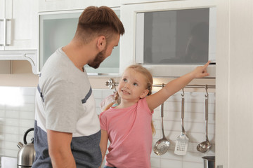 Little daughter and father using microwave oven in kitchen
