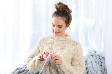 Portrait of beautiful teenage girl in warm cozy sweater knitting at home