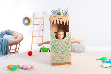 Cute little boy playing with cardboard dragon at home