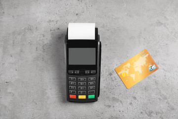 Modern payment terminal and credit card on grey background, top view. Space for text