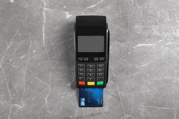 Modern payment terminal with credit card on grey background, top view