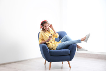 Fototapeta Young woman listening to music in armchair at home. Space for text obraz