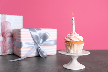 Composition with birthday cupcake and presents on table. Space for text