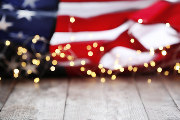 Blurred lights and American flag on wooden table. Mockup for design
