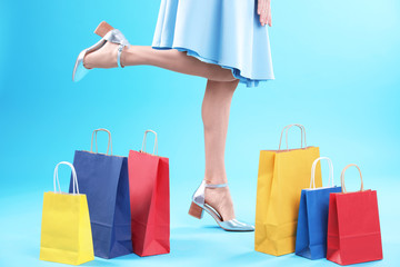 Young woman with shopping bags on color background, closeup of legs