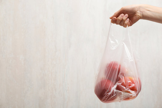 Woman holding plastic bag with apples on light background, closeup. Space for text