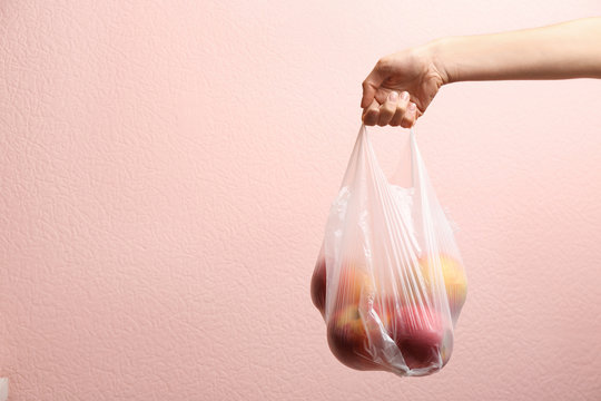 Woman holding plastic bag with apples on color background, closeup. Space for text
