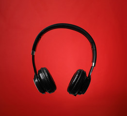 Stylish modern headphones with earmuffs on color background