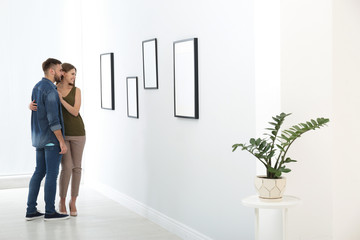 Young couple viewing exposition in modern art gallery