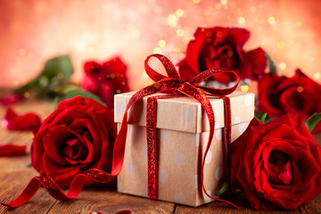 Gift box with red ribbon bow and red roses