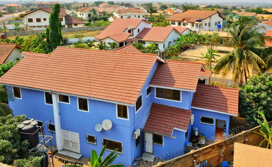 Residential area in West Africa. Top view on family houses, yards with gardens, surrounded by fences & roads. Modern lifestyle in developing countries. Beautiful urban landscape. Ghana, Accra, Tema