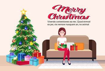 woman sitting on couch modern living room merry christmas happy new year decorated gift boxes pine tree flat horizontal copy space