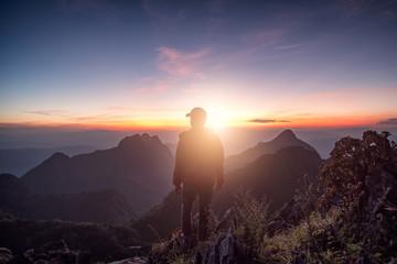 Man traveler standing on rock ridge with sunlight in wildlife sanctuary