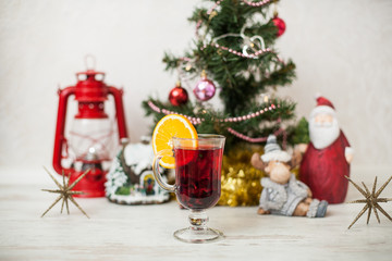 Christmas decor, tree, gold pumpkin, deer, gift, Santa, star, gingerbread house, red lantern on the wooden table. White wood background Hot mulled wine drink with orange in a glass cup Christmas eve