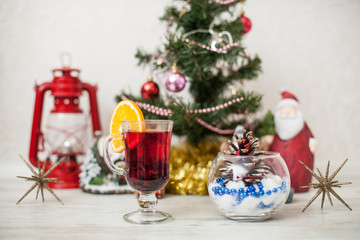 Christmas decor, tree, gold pumpkin, bump in glass vase, red lantern on the wooden table. White wood background Hot mulled wine drink with orange in a glass cup Christmas eve