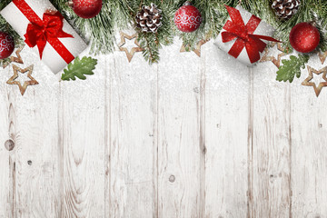 Frosty Christmas decorations and gifts covered with snowflakes on white wooden background. Christmas background with free space for text