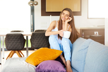 Smiling young woman daydreaming on the sofa at home
