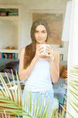 Young woman wearing pajamas and drinking her coffee at home