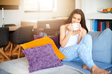 Beautiful young woman relaxing on sofa at home early morning and drinking tea
